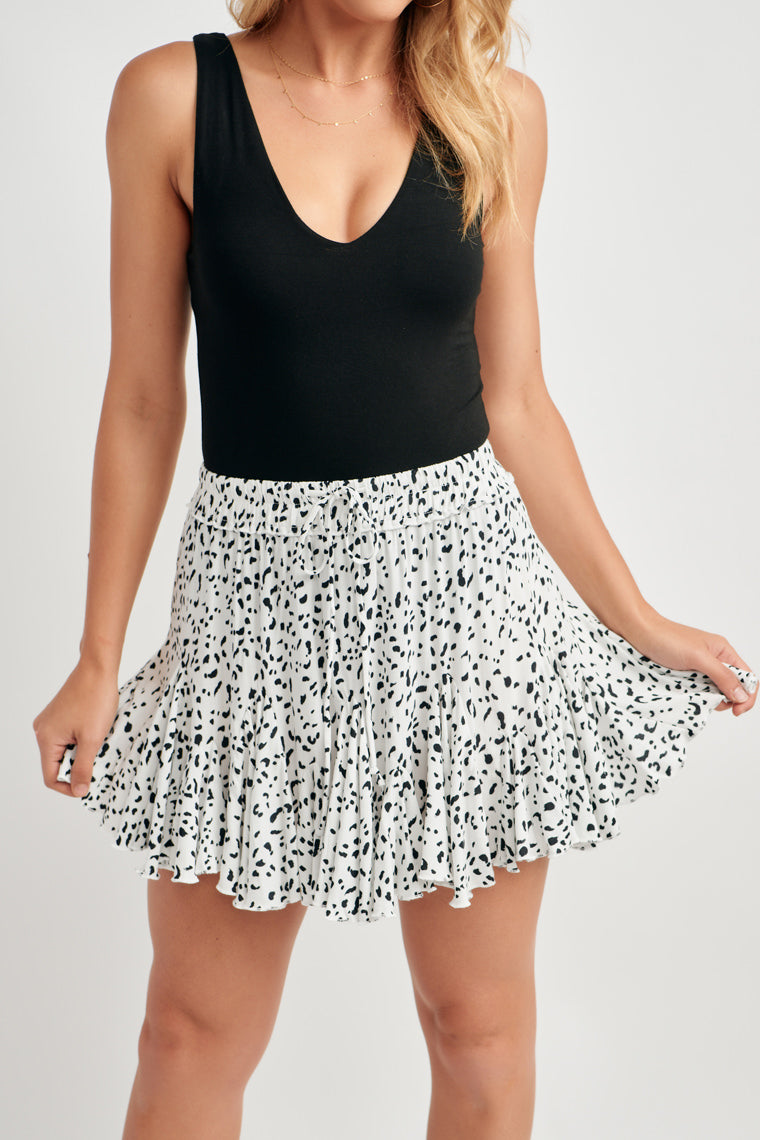 This white and black dot printed skirt features an elasticized drawstring waistline that carries into a skater mini skirt with triangular pleats for extra frill