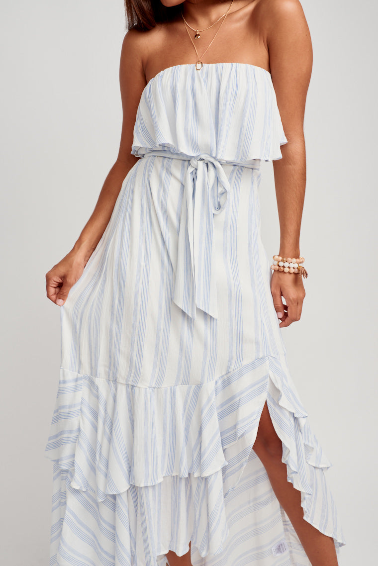 This striped dress has a straight neckline with a smocked flounce bodice that leads to a flowy asymmetrical layered ruffle hem skirt. Features a fabric tie to secure at waist.