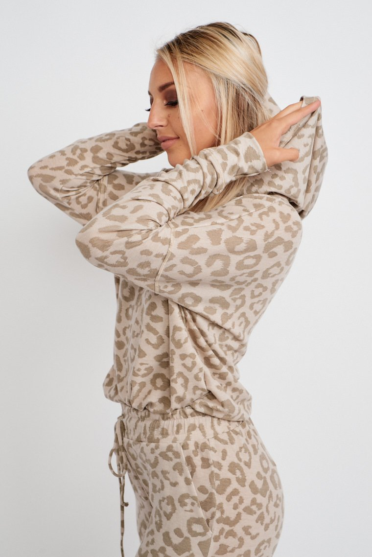 Leopard spots speckle the fabric of this super cozy hoodie. Long sleeves attach to hooded and relaxed bodice silhouette.