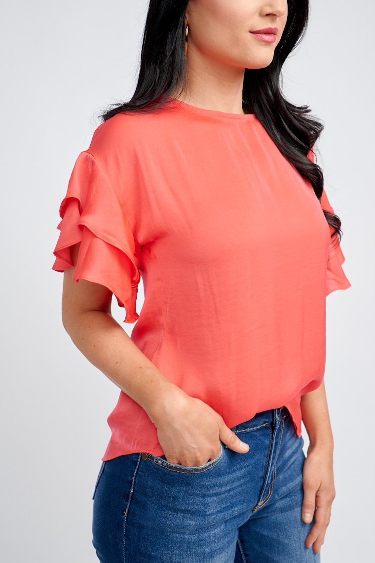 Short tiered ruffle sleeves that attach to a u-neckline on a relaxed and oversized fit bodice silhouette that meets at the waist. Features a zipper closure down the back.