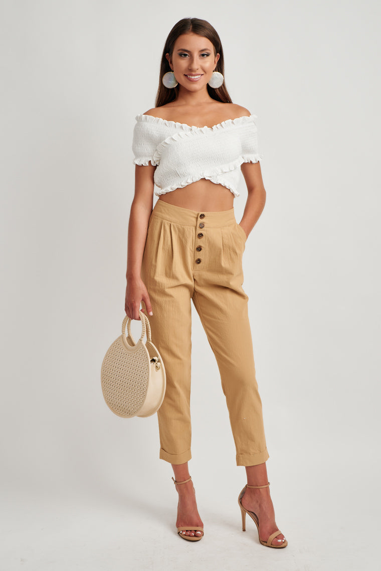 An off the shoulder, smocked bodice creates a criss-cross feature across the bodice with a cropped hem.