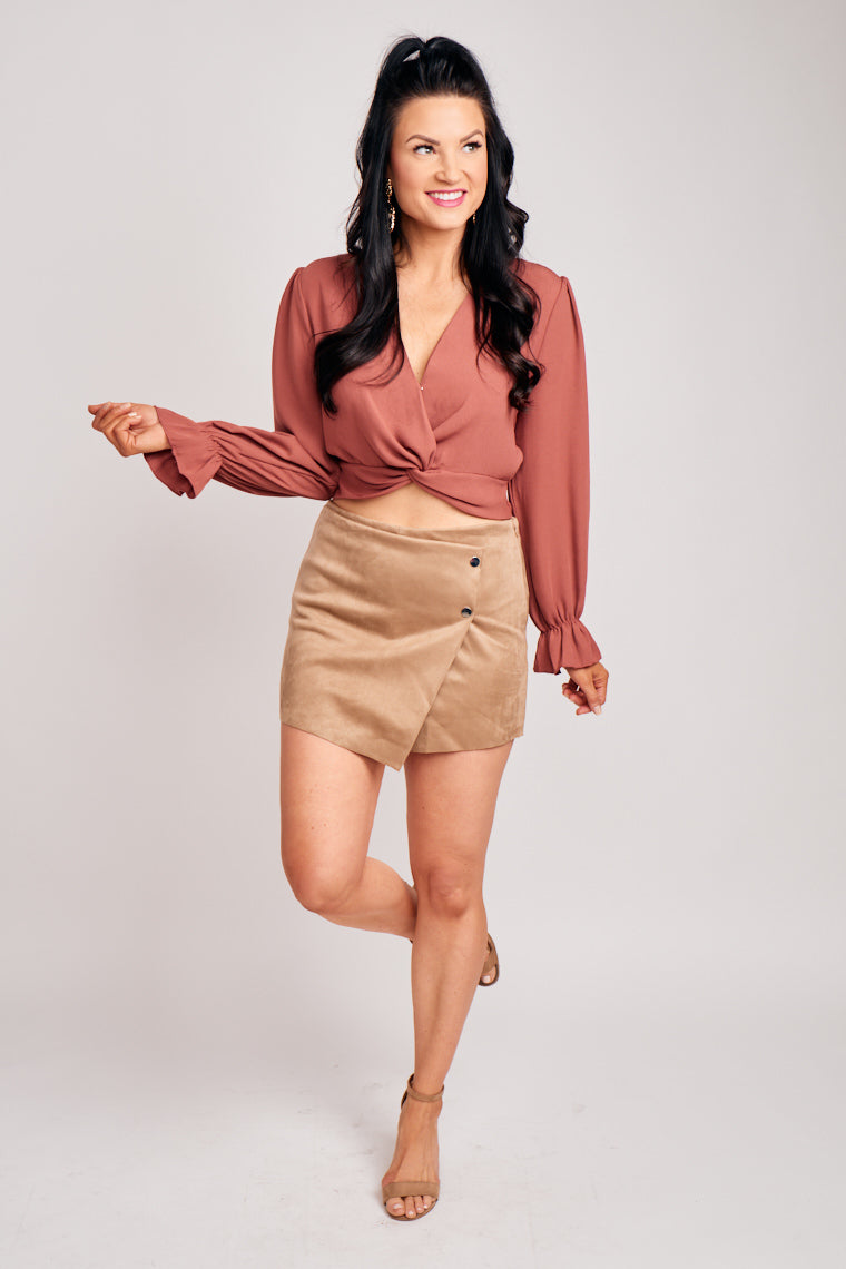 Fitted waistband leads to a skirt panel with button details at the side atop of comfortable fitted shorts. This skort features a zipper on the side.