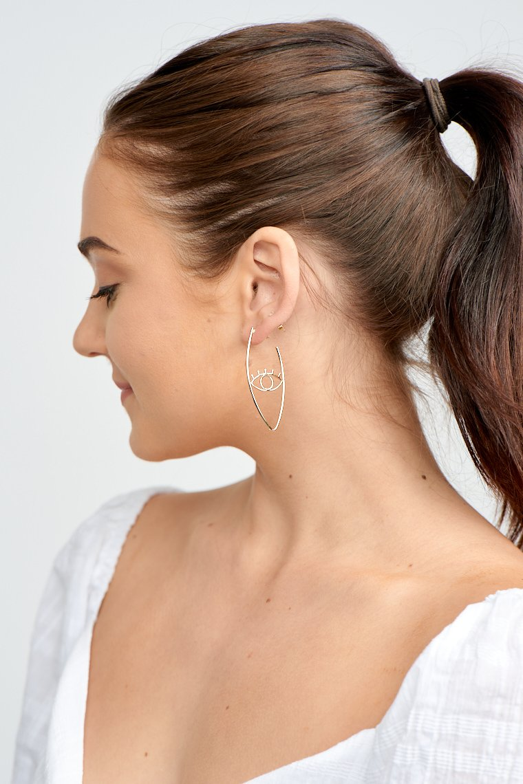 These earrings have a post that goes down to an oval outline with an eye-shaped wire detail at the center.