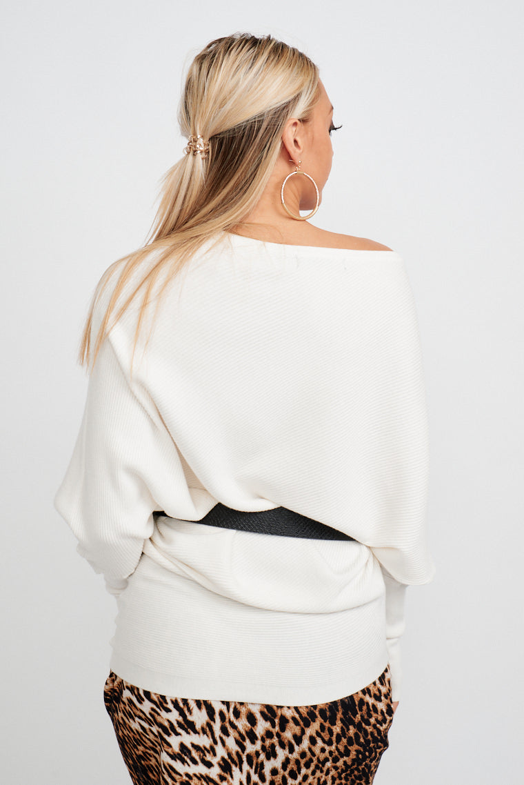 Long fitted sleeves that attach to a high straight and asymmetrical neckline that is on an oversized bodice silhouette and goes down into a fitted opening at the waist.