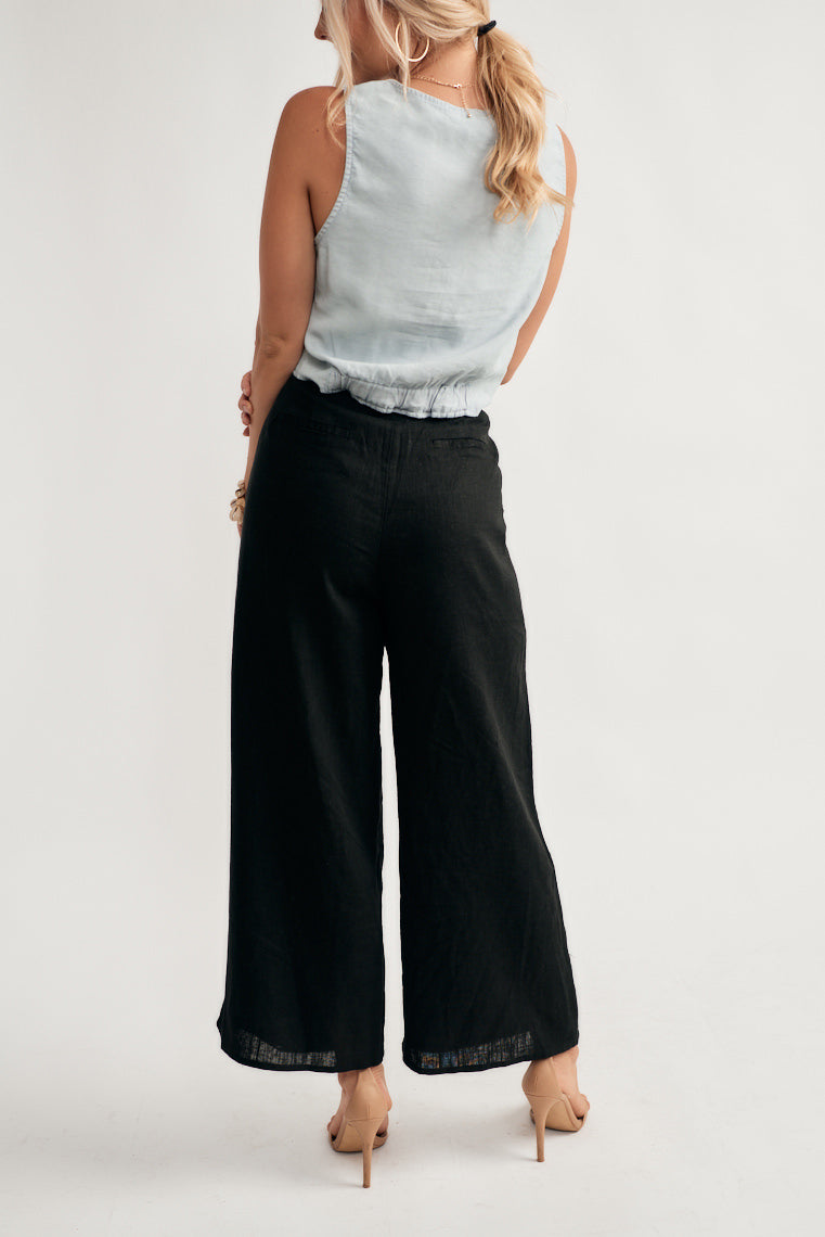 This lightweight, black linen woven pants feature a high-rise fit on the banded waistline with an exposed, button up fly with a straight, wide pant leg.