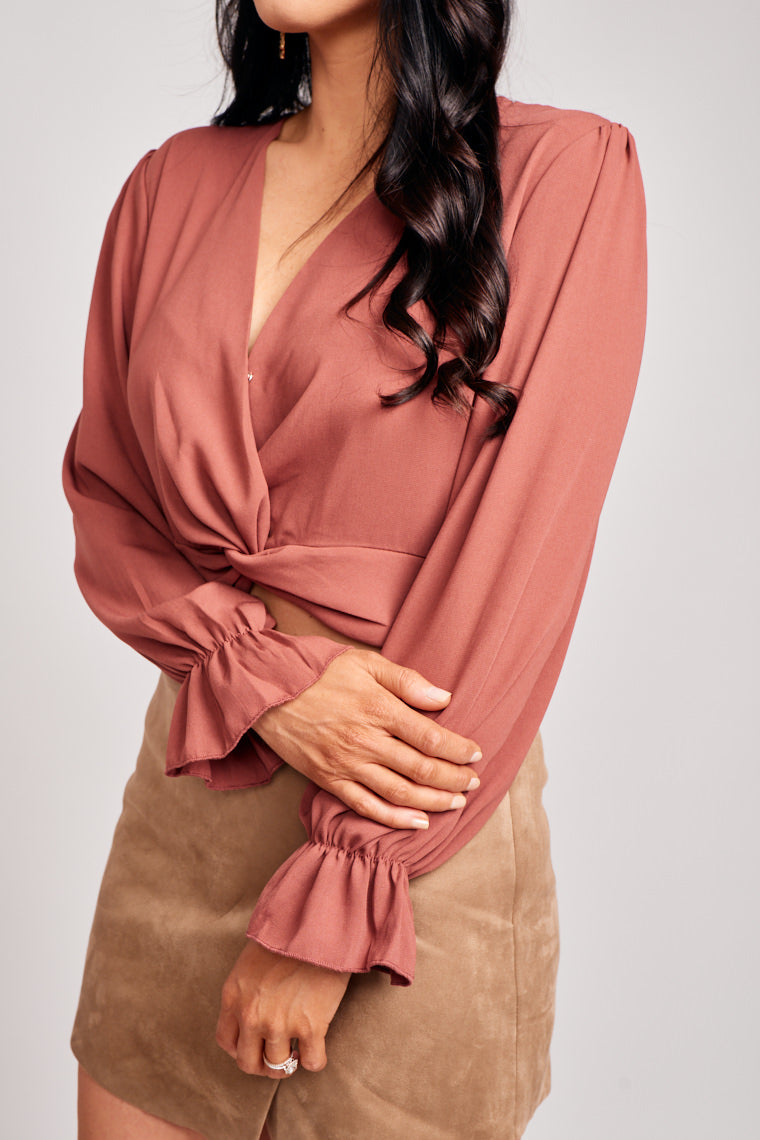 Long elastic cuff ruffle sleeves attach to a surplice neckline into a relaxed bodice silhouette with banded twist detail at the waistband. Features a modesty closure.