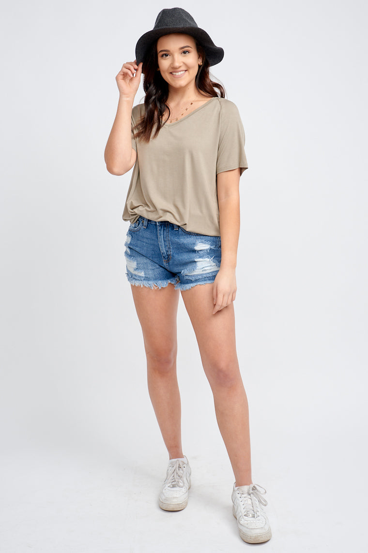 Medium washed shorts have a fitted button and zipper waistband with a traditional 5-pocket structure. It has distressed details across the shorts and leads to a raw frayed hem.
