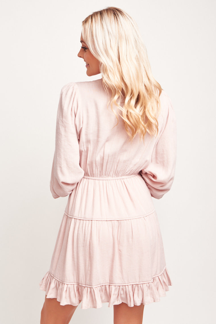 High ruffle neck hem with banded v-neckline and a drawstring tie. Long cuffed sleeves attach to a relaxed bodice meets waistband and a tiered ruffle skirt.