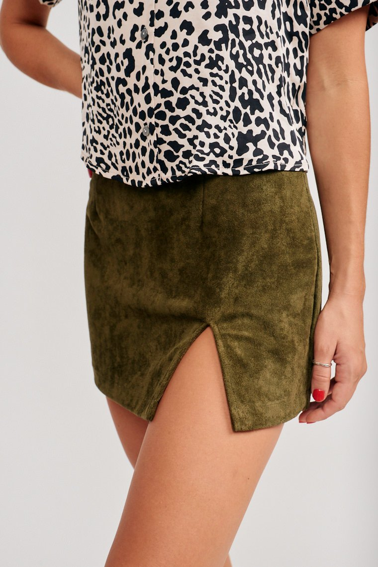 This olive skirt has a fitted waistband and leads to a darted and mini pencil silhouette with a slit at the side of the panel. This skirt features a zipper with a hook and eye closure.