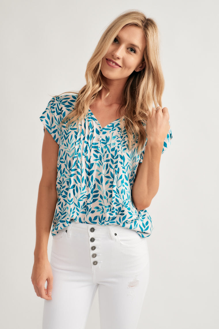 Shades of blue in a playful leaf print decorates this lightweight blouse with tulip short sleeves on a folded pleat-detailed bodice with a v-neckline and rounded hem.