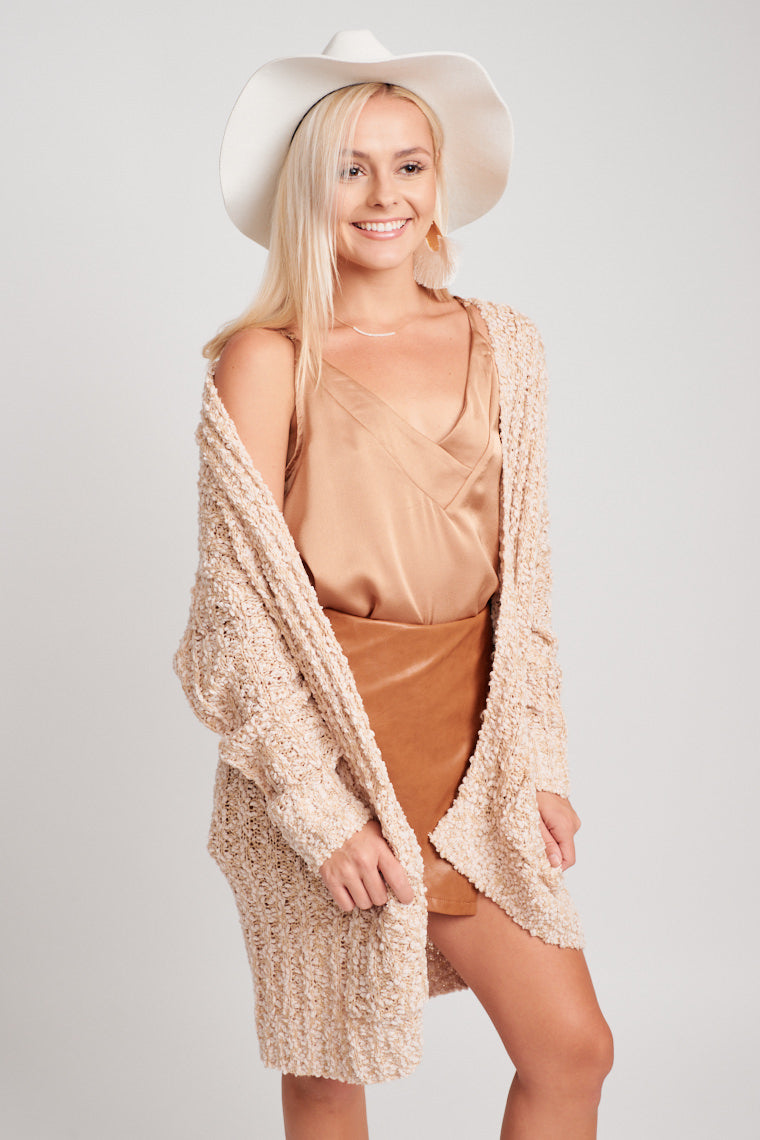 This buttonless cardigan has long sleeves that attach to an extended and open bodice with pockets on the front panels. Pair atop of your weekday look.