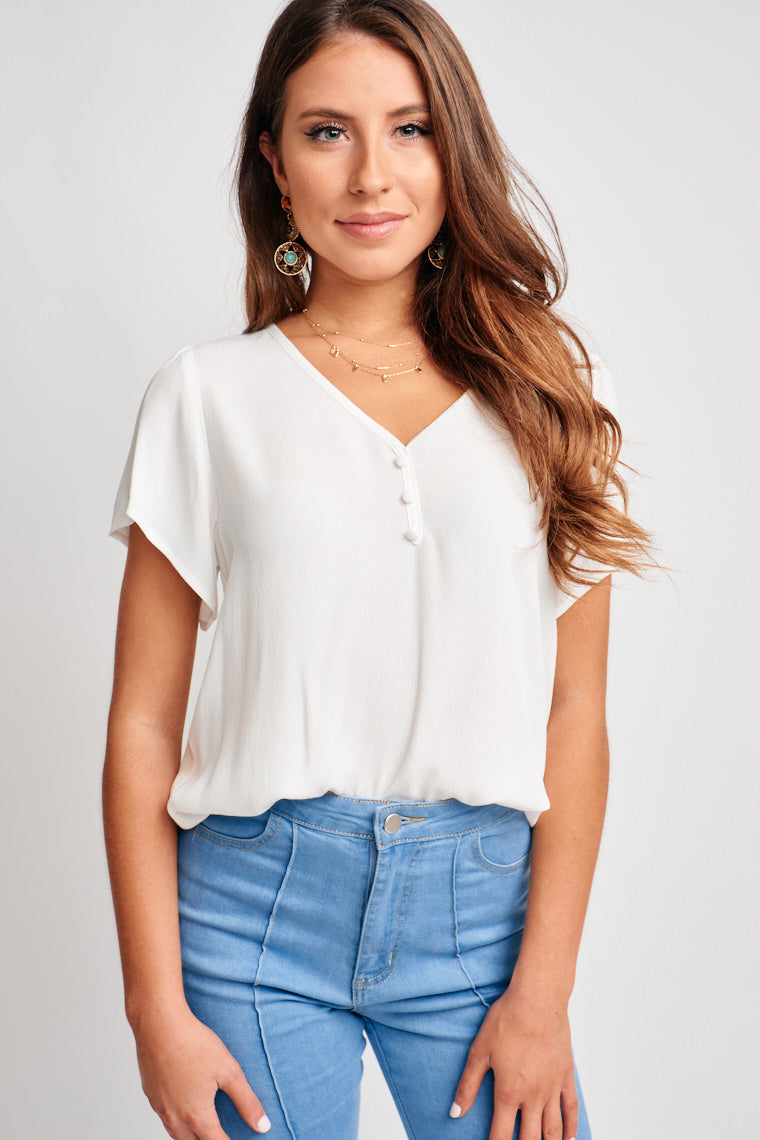 Short sleeves attach to a v-neckline with a button-detail and lead to a relaxed and comfortable bodice silhouette. Pair with printed pants, gold hoops, and a simple necklace!