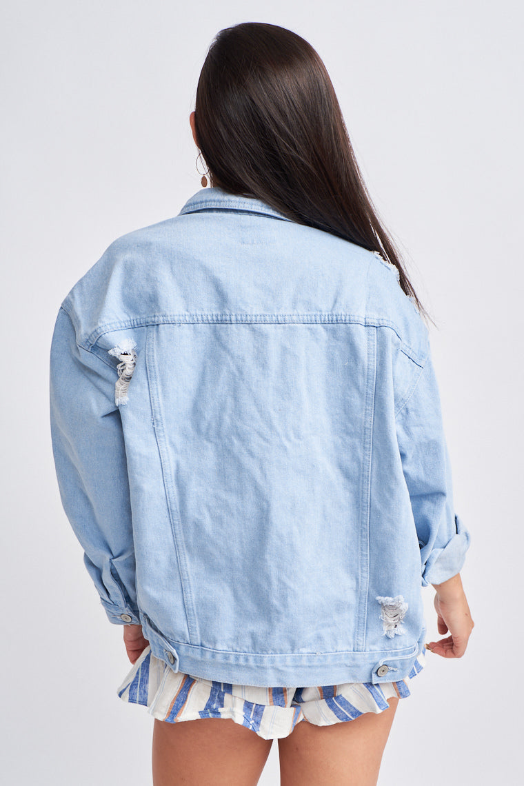 Long button cuffed sleeves attach to a collared neckline on a paneled and oversized boyfriend button-down bodice. It has distressed details across the front and back.