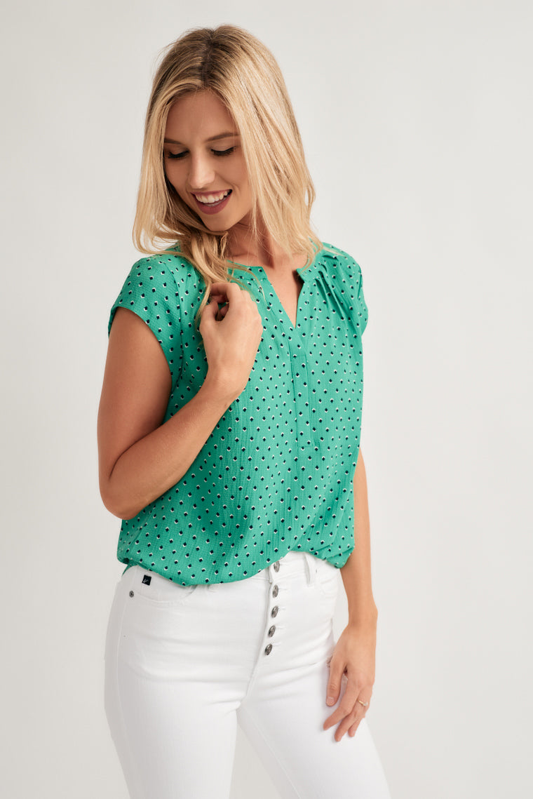 Black and white dot print decorates this elegant green blouse with a collarless, v-neckline with pleat details around the neck and a relaxed bodice with cap sleeves.