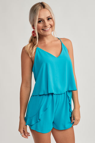 551a3a8e11 This lightweight blue romper features thin straps on a v-neckline with a  racer
