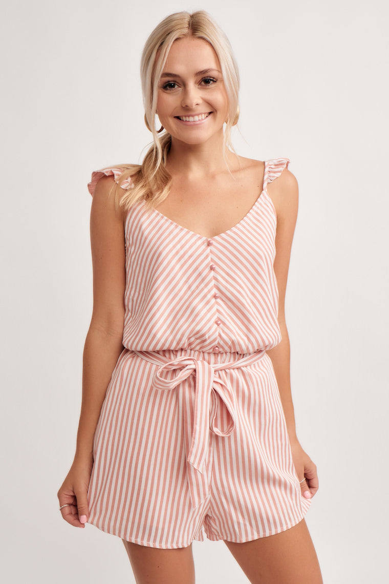 Pink and white stripes, flutter sleeves on thin straps, down to a gentle v-neckline and into a button detailed bodice atop a cinched waistline and relaxed shorts.
