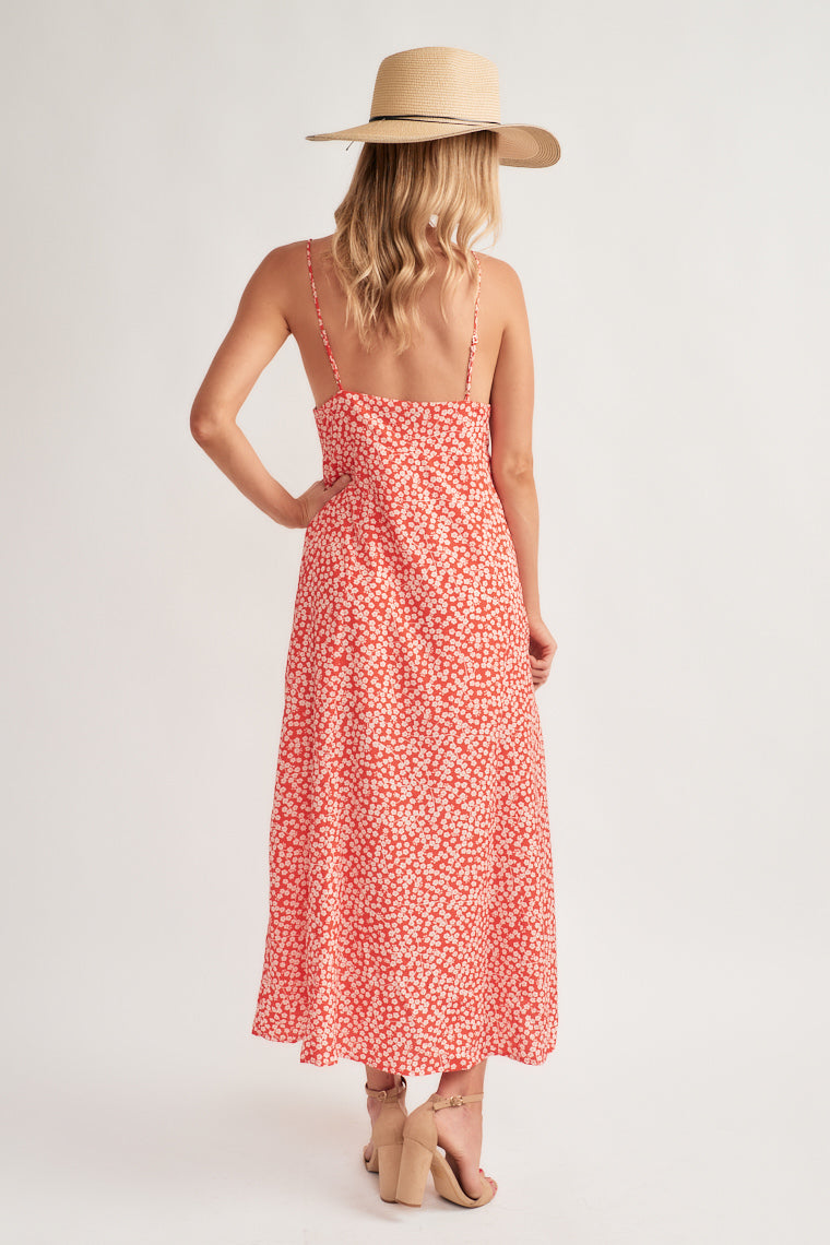 Floral maxi with adjustable skinny straps supporting a triangle, ascending point bodice with a banded waistline and buttons down the center A-line silhouette.