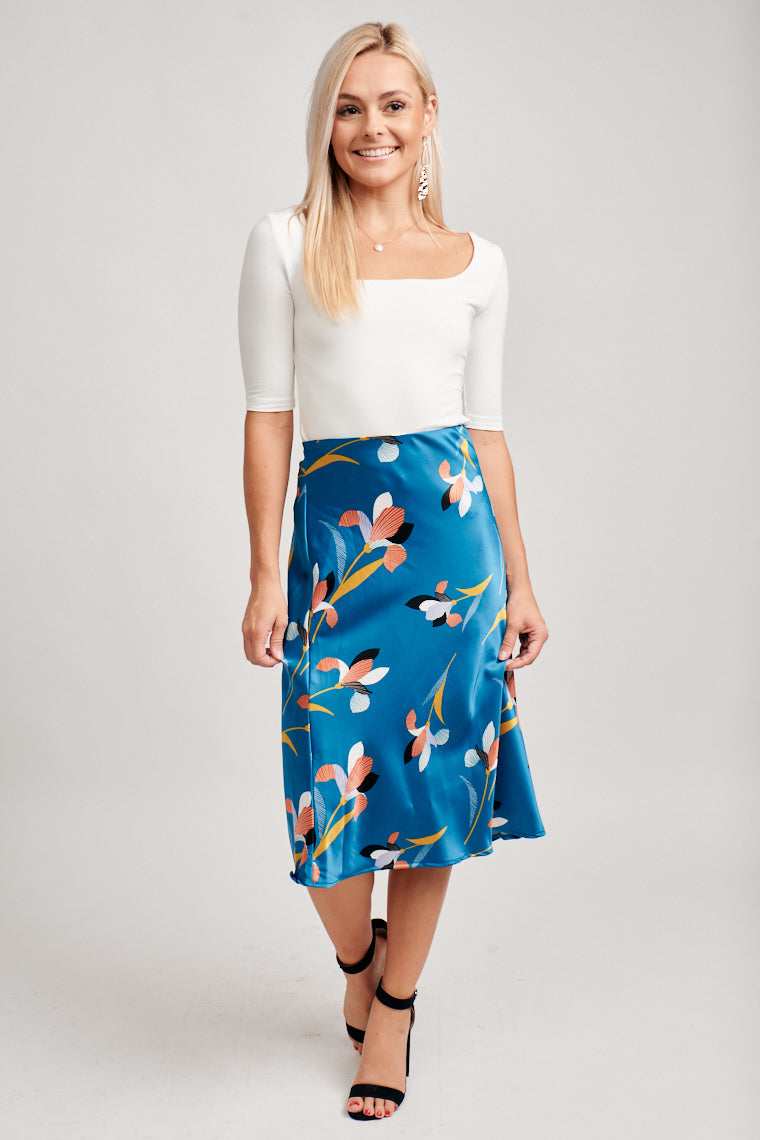 This midi skirt has multi-colored floral prints across this satin fabric. It has an elastic waistband that hugs at the waist and hips and flows down to pencil silhouette.