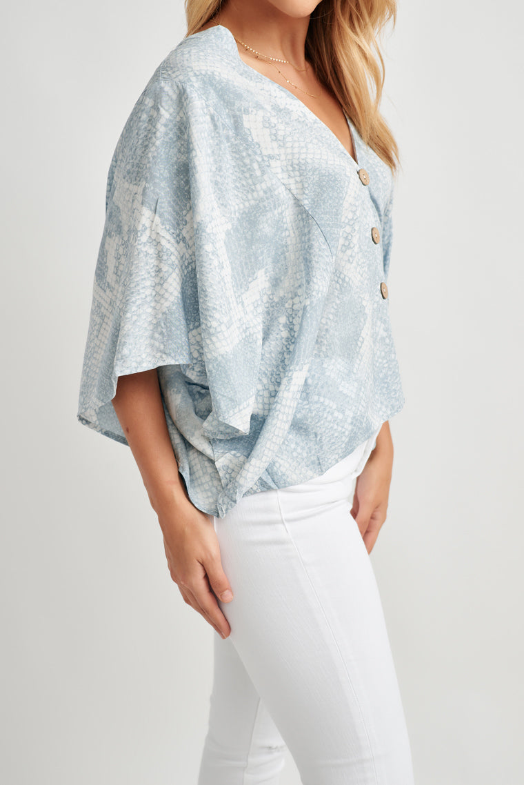 This gorgeous blue and white snakeskin print creates a v-neckline with an oversized, flowy, relaxed fit blouse with kimono sleeves and button-down center.