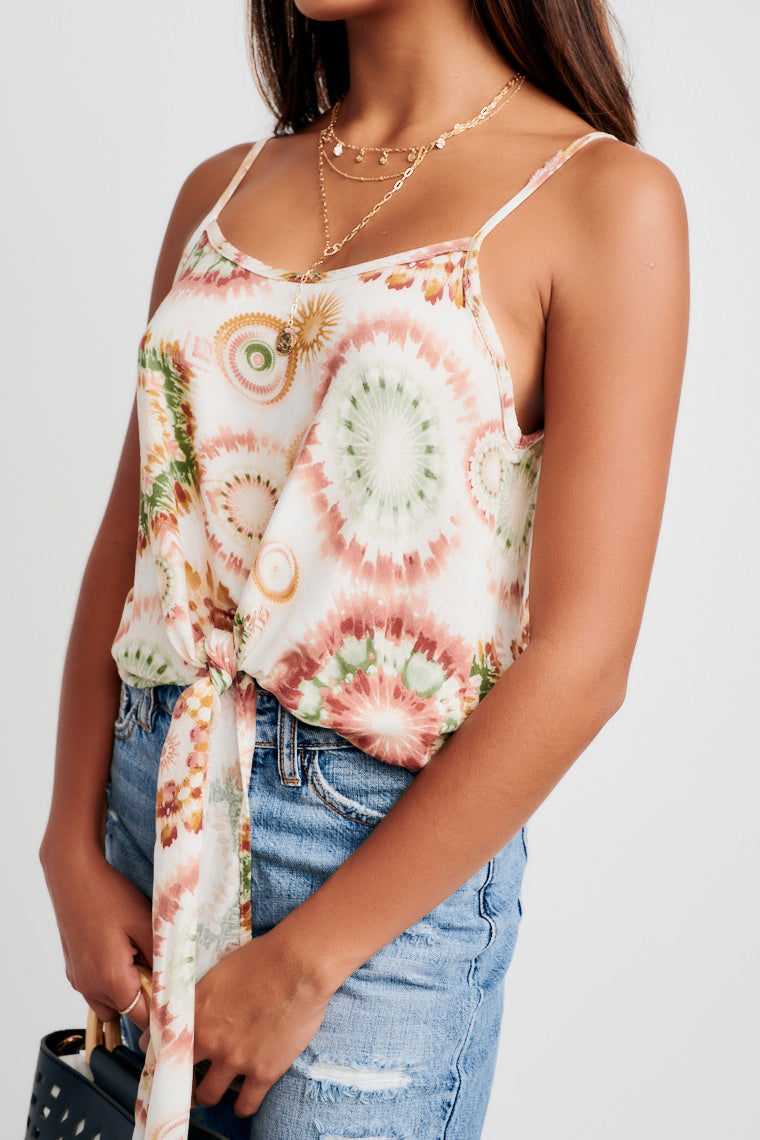 Red, orange, and green prints cover this tank top. It has skinny straps attached to a rounded u-neckline and relaxed bodice with tie-front hem.