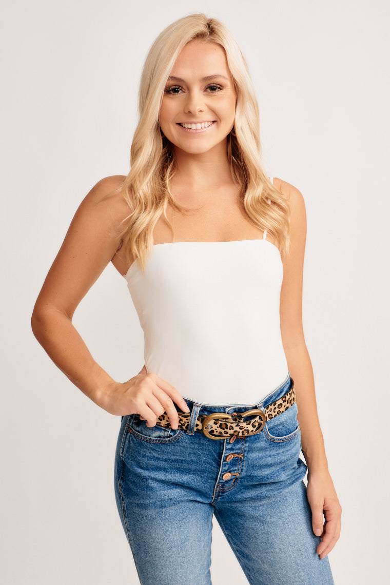 Ultra-soft, stretch knit in ivory shapes this straight neckline with supporting skinny straps on a double lined, fitted bodice and cutely cropped hem.