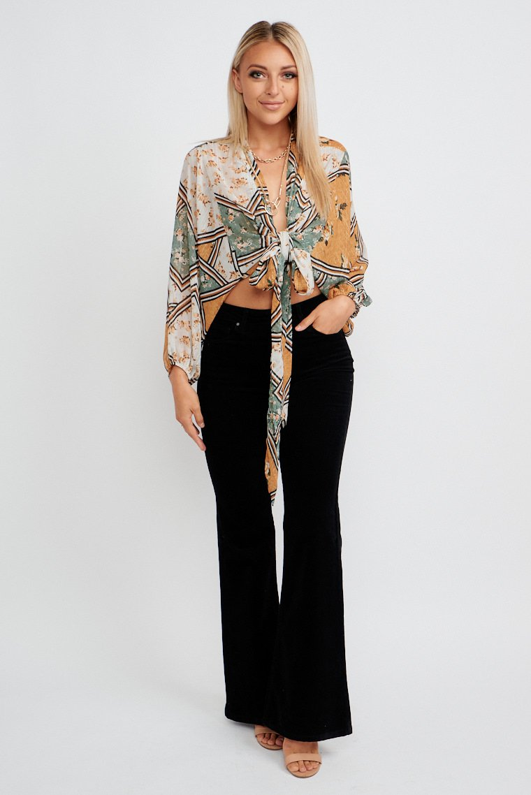 This printed top has long elastic cuff sleeves that attach to a deep v neckline leading to a tie-front hem which creates a cropped and relaxed fit bodice silhouette.