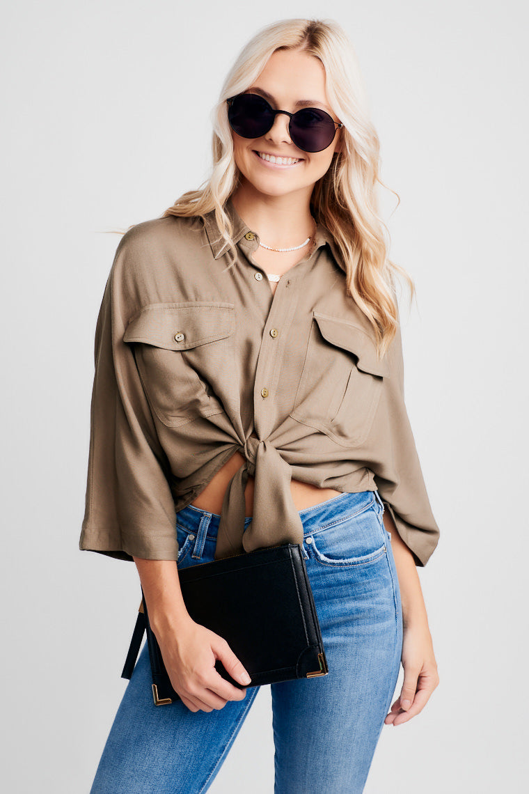 This olive collared top features a relaxed button-up bodice, front pockets, and tie-front hem. Style with sandals or booties and jeans for an easy look!