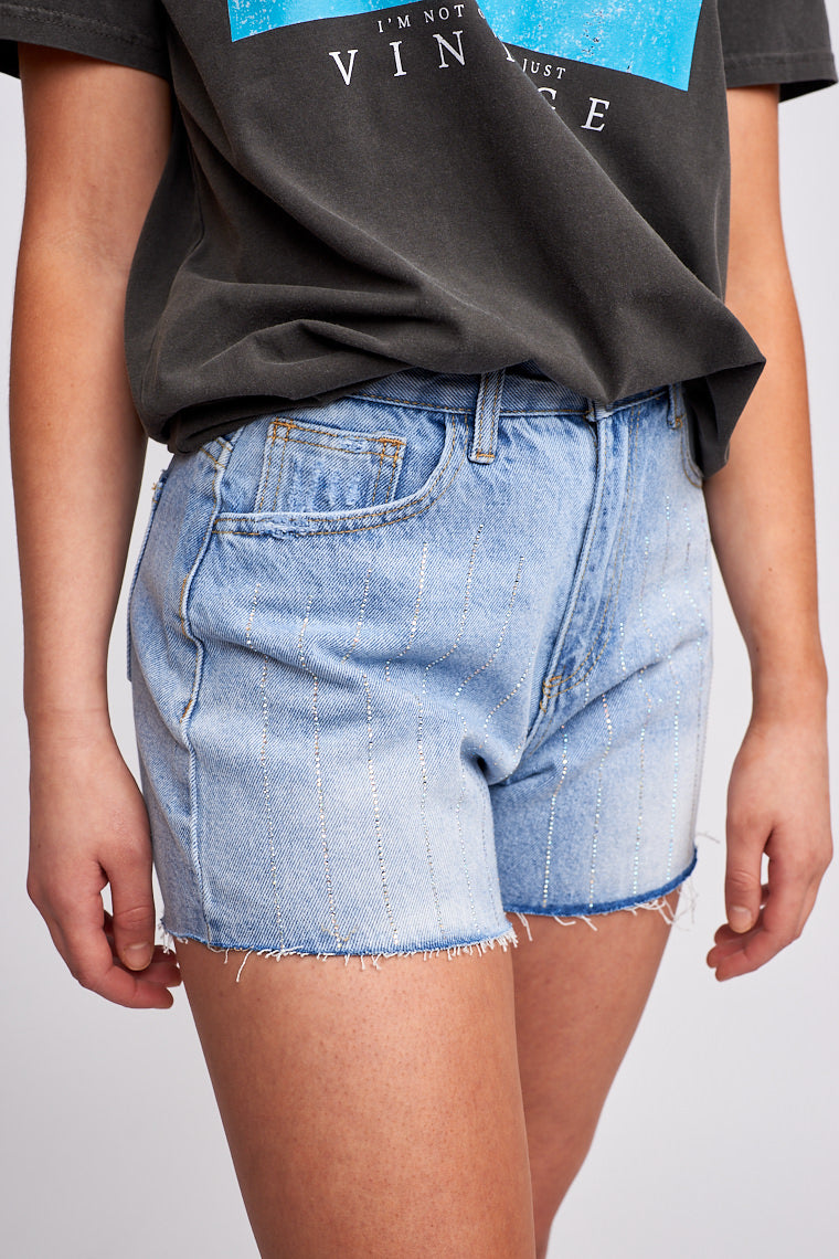 Fitted button and zipper waistband with a traditional 5-pocket structure. It has striped rhinestone details that go down the shorts and leads to a raw hem for a fun flair.