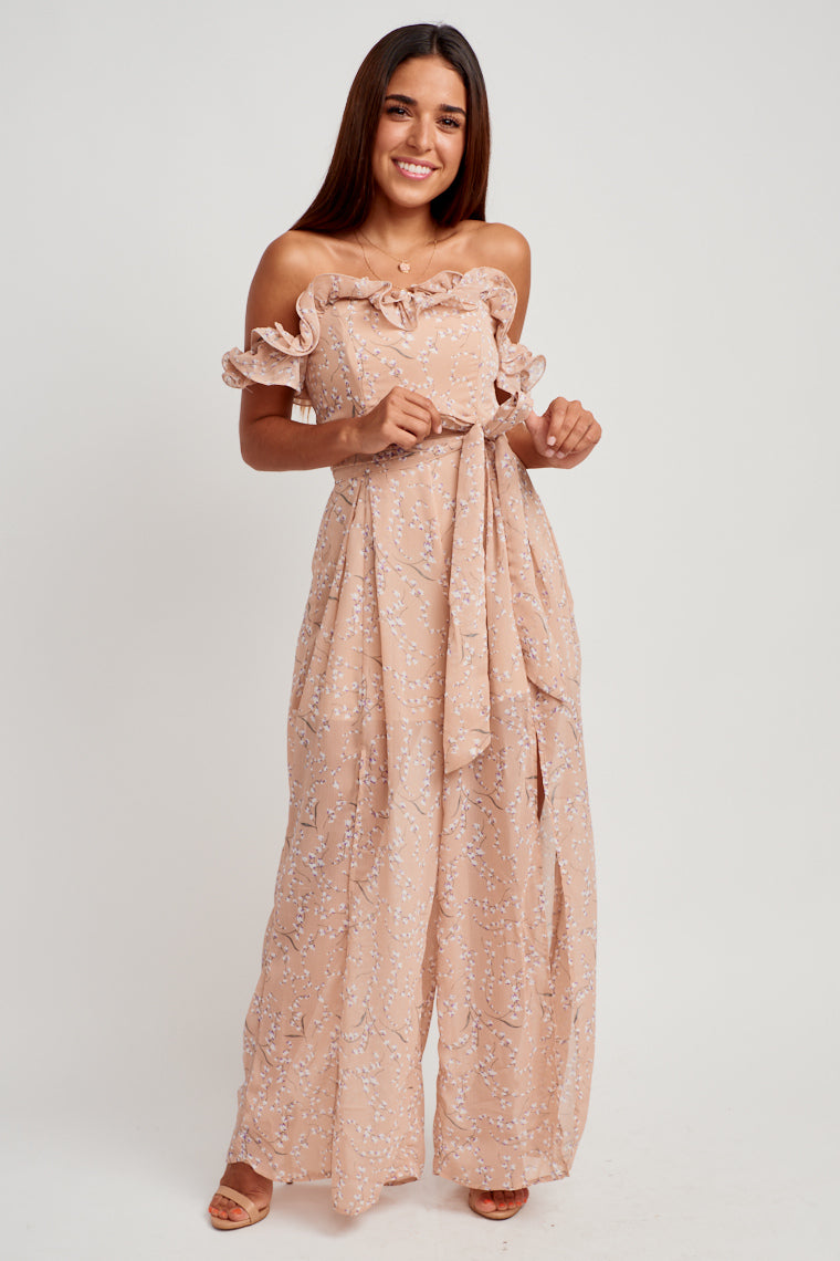 Off the shoulder ruffles and a sweetheart neckline that meets a darted and boned bodice. At the darted and tie front waist, extends into flowy pant legs with open slits.