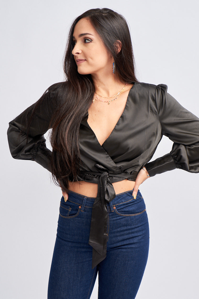Long banded puffed sleeves attach to a surplice neckline on a relaxed fit cropped bodice with an elastic waistband. Tie that comes from the side that could be tied at the front.