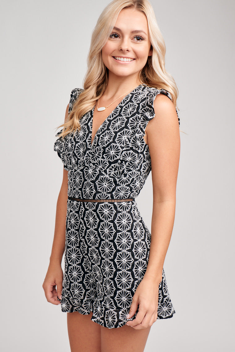 Fitted bodice with a deep v-neckline. Ruffle sleeve details that come from the back drape to the front meets a banded waist detail before leading to fitted shorts.
