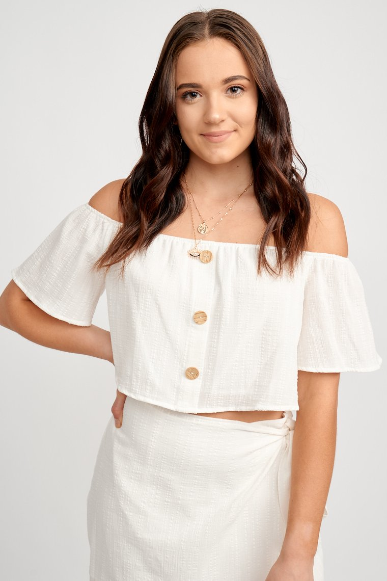 Short off-the-shoulder sleeves attach to a straight neckline that leads to a relaxed and cropped bodice with button details down the front.