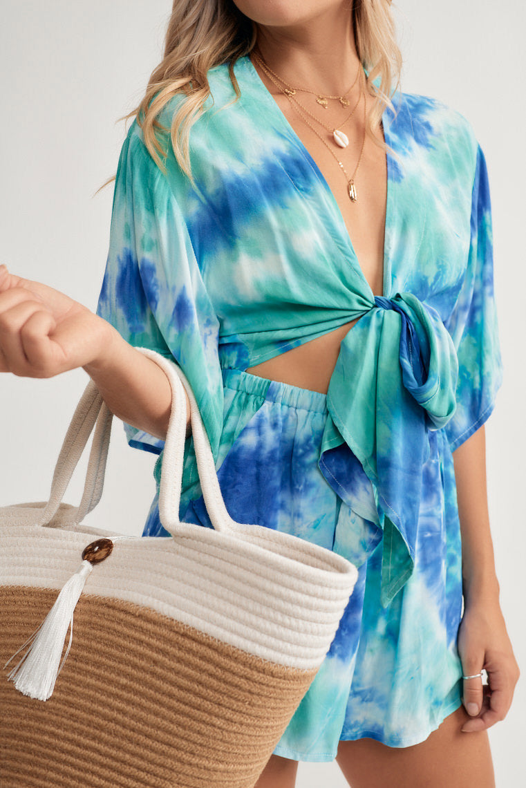 Shades of blue tie-dye decorate this short sleeve romper that offers a tie front neckline leaving a midriff cut out above the cinched waistline and relaxed shorts.