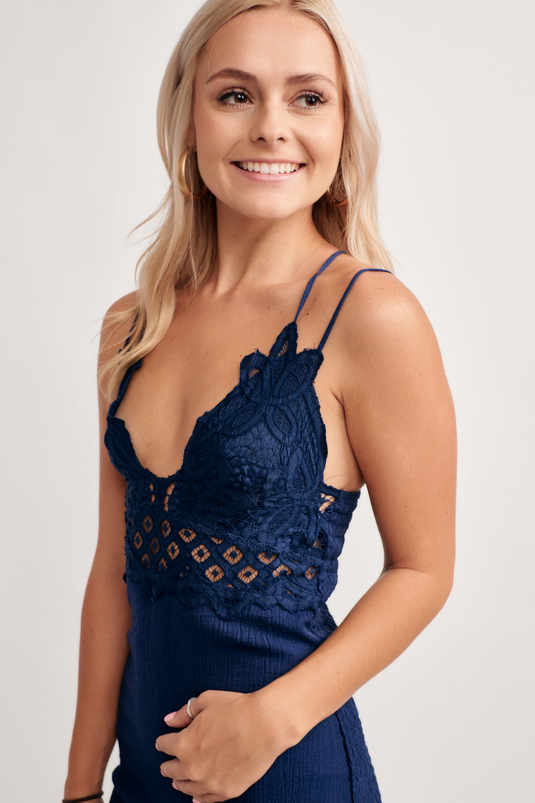 This navy dress offers a scalloped lace overlay on a v-neckline hem with thin straps and is darted across the bodice and goes into a simple hip-hugging skirt.