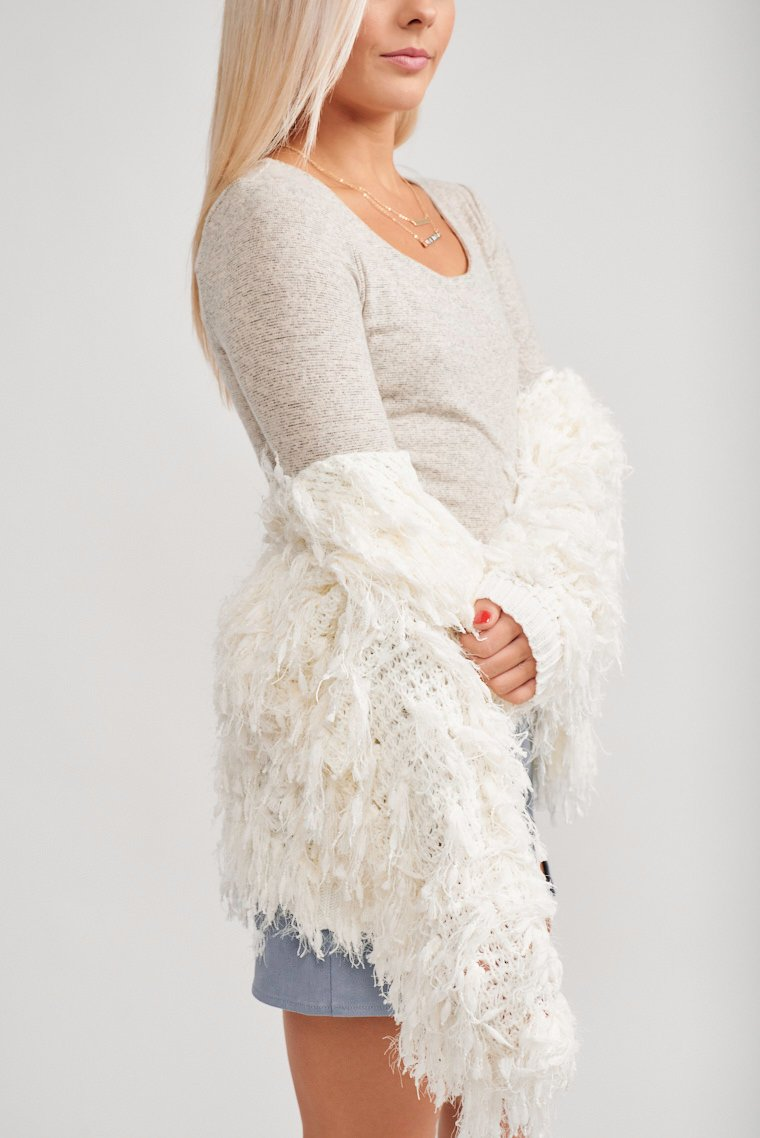 This knit and shaggy fringe covered cardigan has long sleeves that are attached to an open front and relaxed silhouette bodice that ends at the waist.