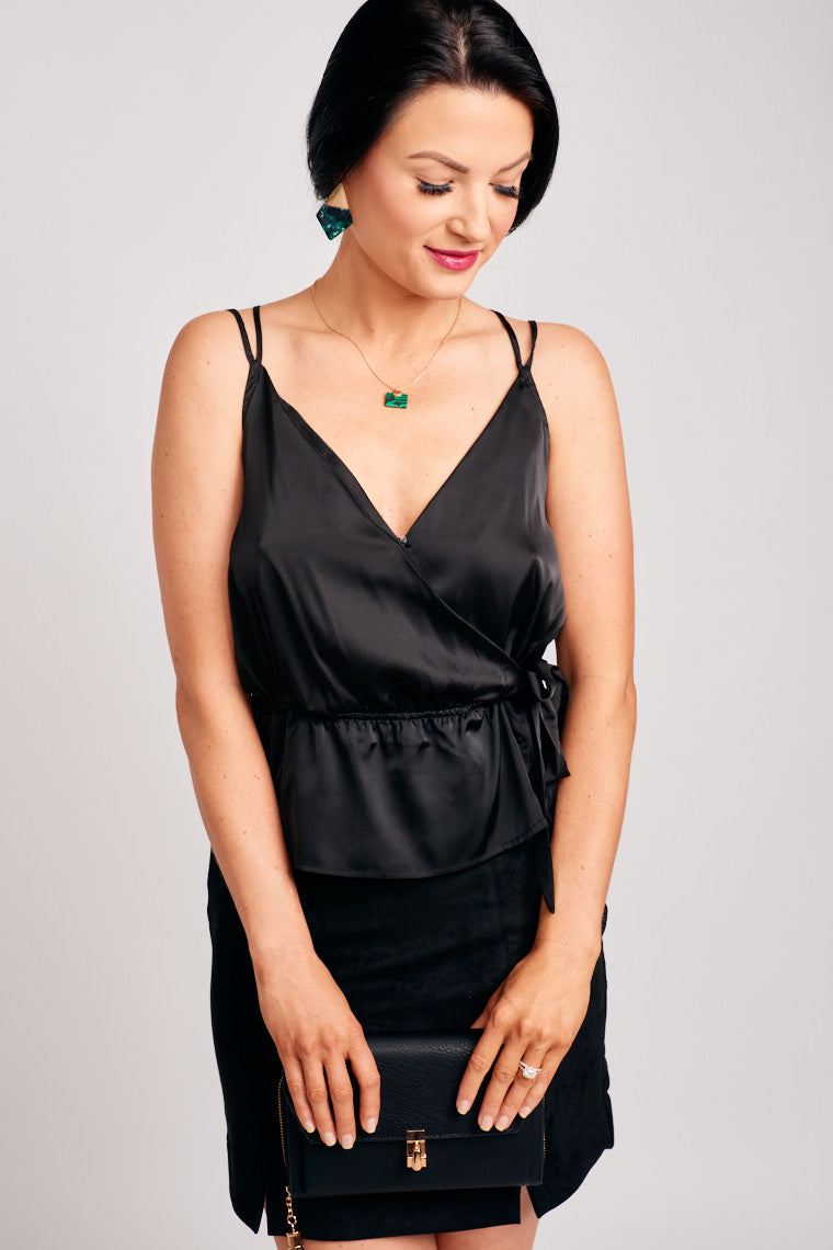 Thin adjustable straps attach to a surplice neckline with a comfortable bodice silhouette lead to a fabric tie at the side with a peplum style flair at the hem.