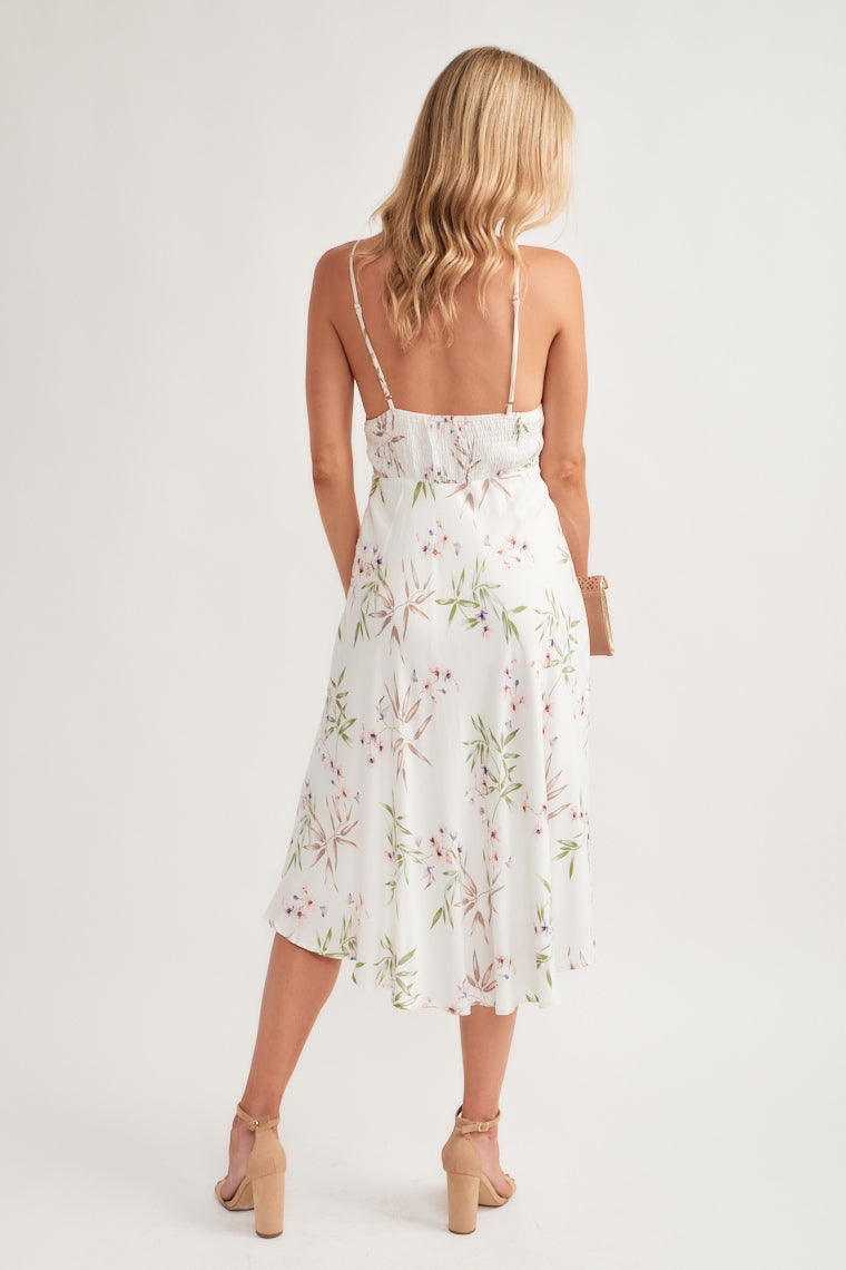 This floral, leaf print maxi features adjustable skinny straps on a triangle bodice with a front banded waistline and smocked back that transitions into a flowy handkerchief midi-length hem.