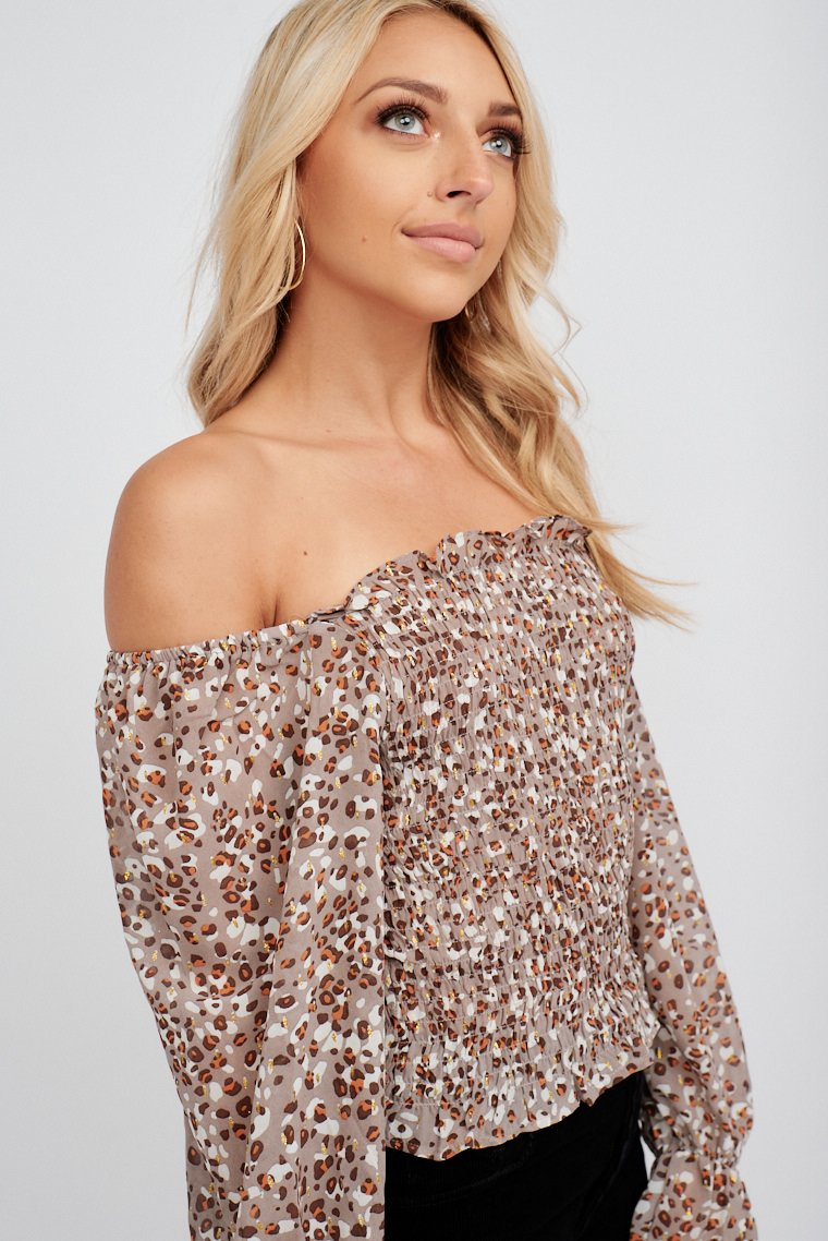 Brown and gold leopard prints, long puffed and ruffle cuff sleeves that attach to a straight and off-the-shoulder neckline on a smocked and fitted bodice silhouette.