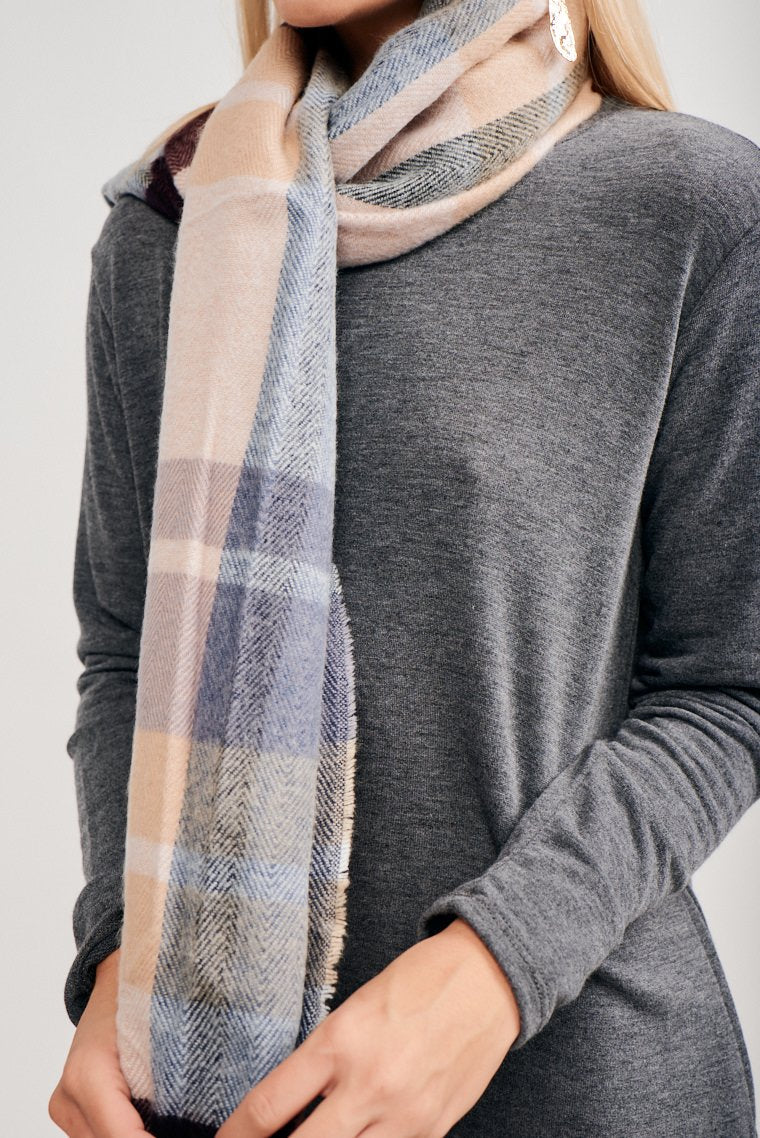 This multi-colored plaid print scarf is long and can be wound around your neck and shoulders to provide some warmth against the breezes.