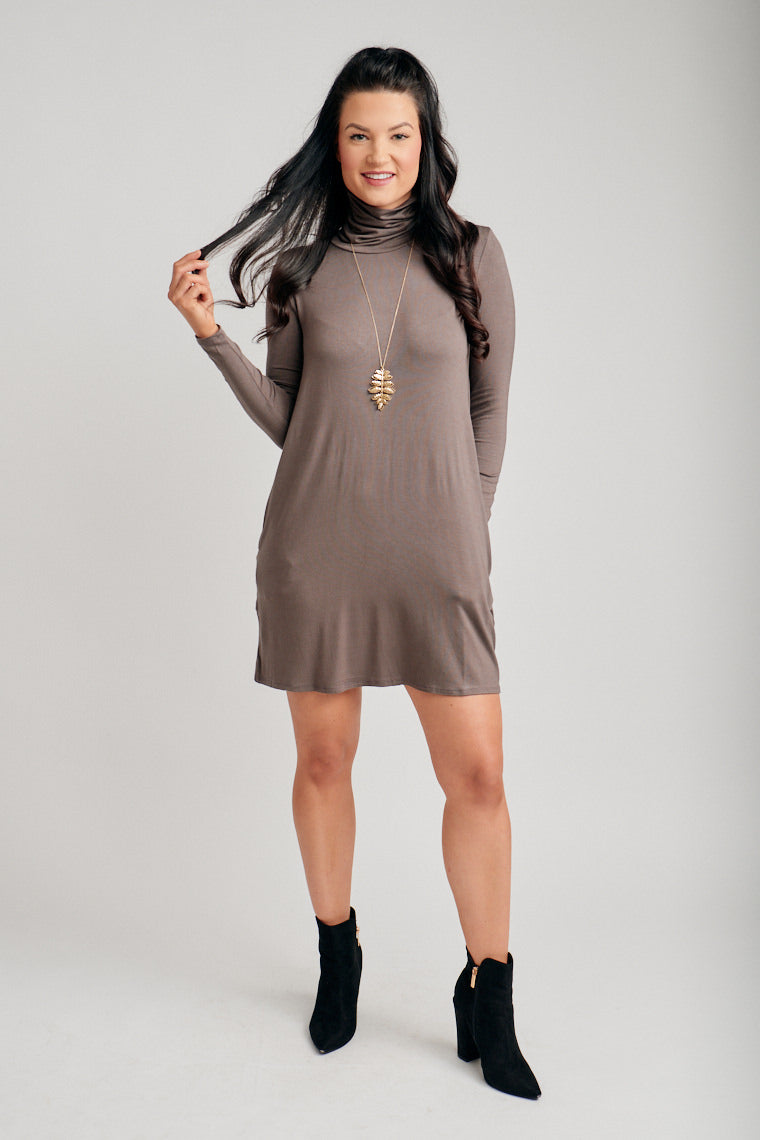 Fitted long sleeves attach to a high turtle neckline and go into a shift silhouette dress with pockets at the side. Style by pairing with thigh-high booties.