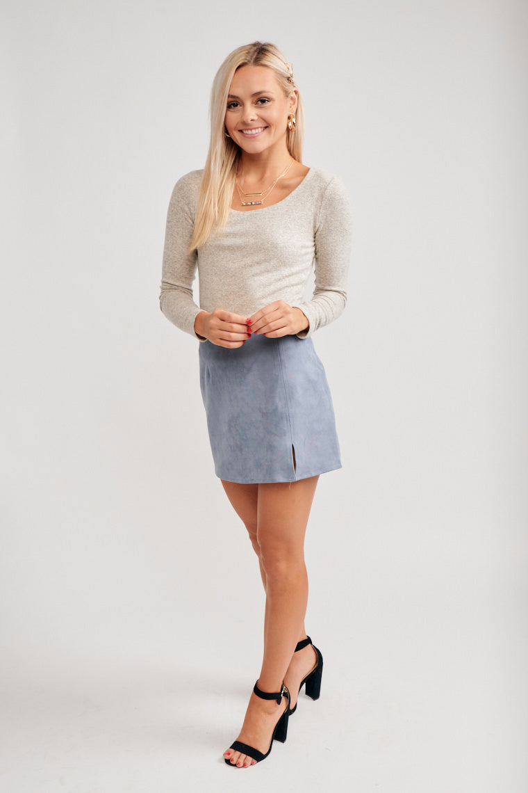 The skirt has a fitted waistband and leads to a darted and mini pencil silhouette with a slit at the side of the panel. This skirt features an exposed zipper detail on the back.