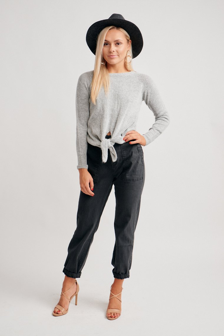 Long sleeves attach to a u-neckline and lead to a comfortable fit bodice silhouette with a tie front hem. Pair with your favorite pair of mid-rise jeans and booties.