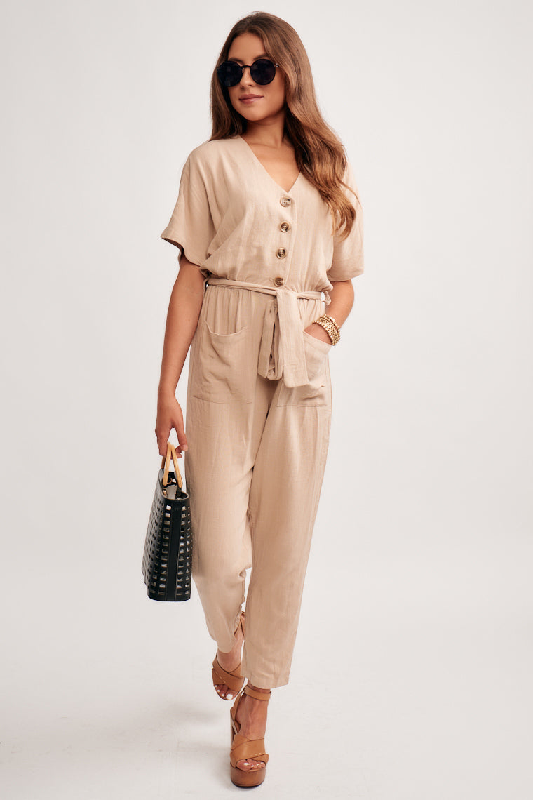 This lightweight jumpsuit offers v-neckline, short sleeves, and button-down closures down the bodice, fabric tie at the cinched waist and pockets down the pants.