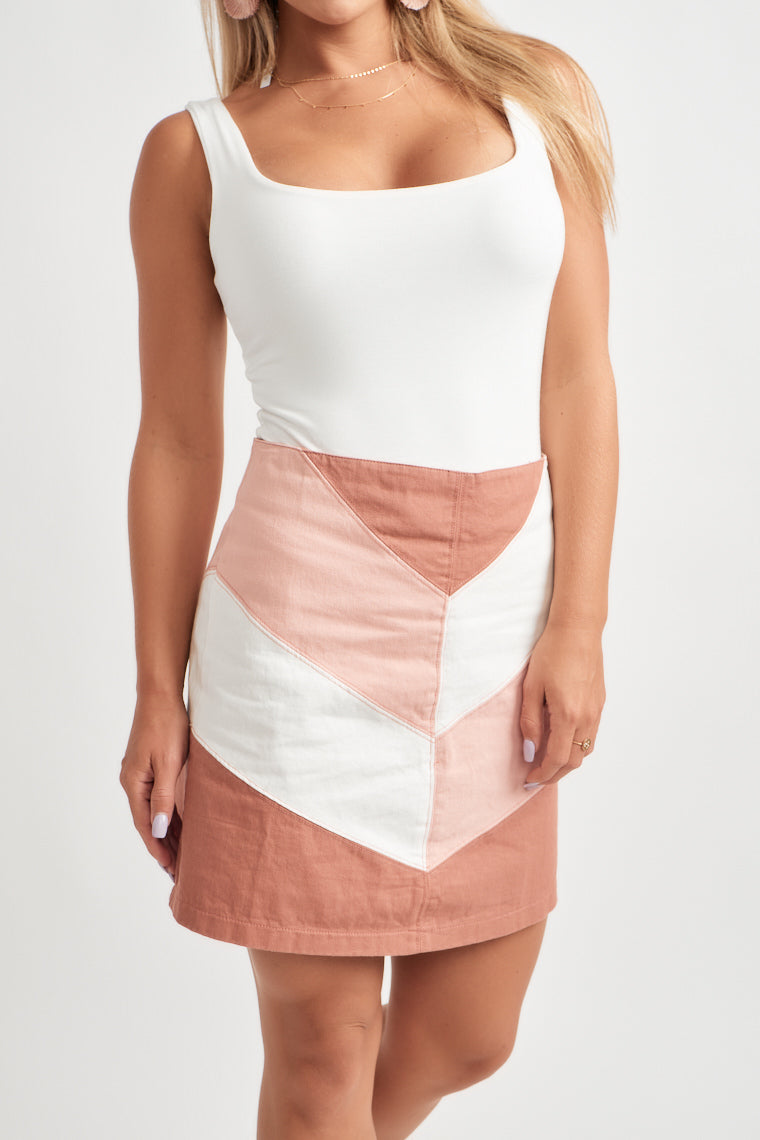 Rust, pink and ivory shades create a color-block pattern on this adorable mini skirt with a fitted waistline and flattering silhouette.