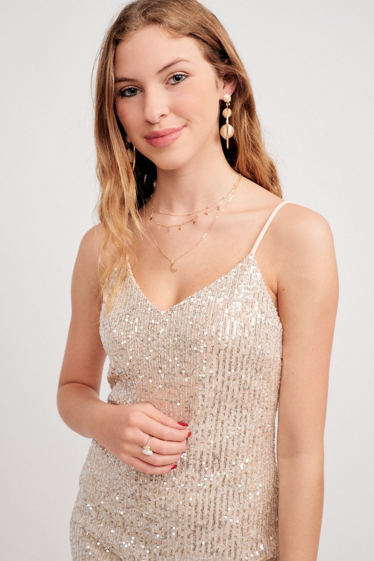 Mini sequins cover the fabric of this shiny dress. Thin adjustable straps attach to a v-neckline and lead into a fitted bodice and skirt silhouette.