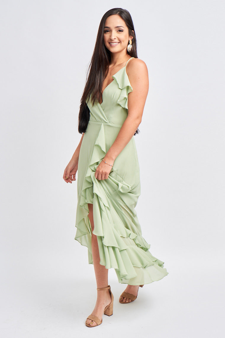 Thin straps reach a ruffle detail on a surplice neckline with a darted bodice and meet a fitted waistband. A cascading ruffle goes down to an open skirt with a layered ruffle hem.