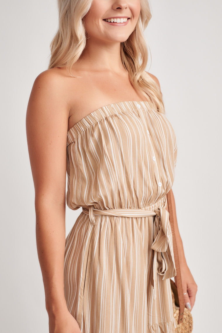 Beige and white striped romper offers a strapless, elasticized neckline with a billowing bodice, cinched waistline and relaxed shorts ruffle at the hem