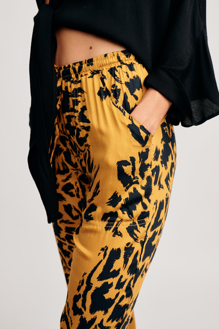 Black leopard prints are spread across lightweight pants, an elastic waistband that leads to side pockets into comfortable loose legs that are cuffed with elastic at the ankle.