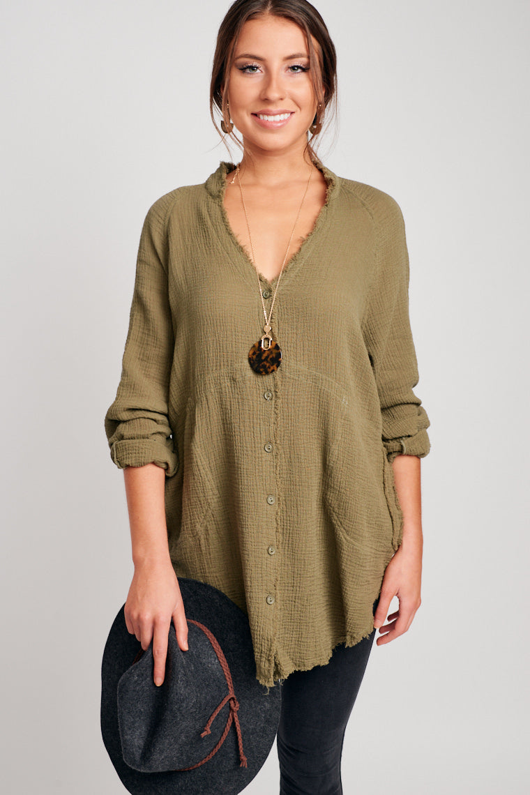 This tunic has long sleeves that attach to a distressed hem v-neckline and leads to a button-down and oversized bodice silhouette with a distressed hem.