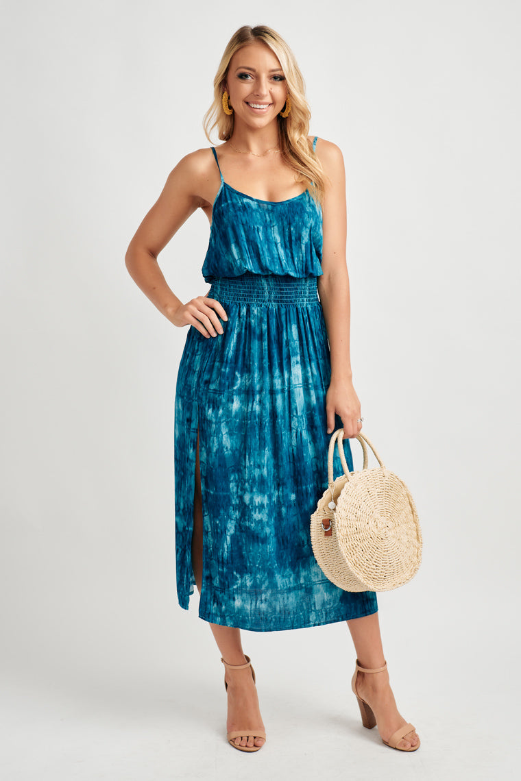 Baby blue and navy tie-dye decorate this adjustable strap, scoop neckline that blouses smocked waistline and flows into a straight midi skirt with a side slit.